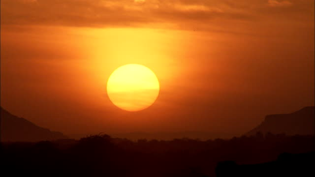 a golden sun glows in a brilliant orange sky above the shibam desert. - yemen stock videos & royalty-free footage