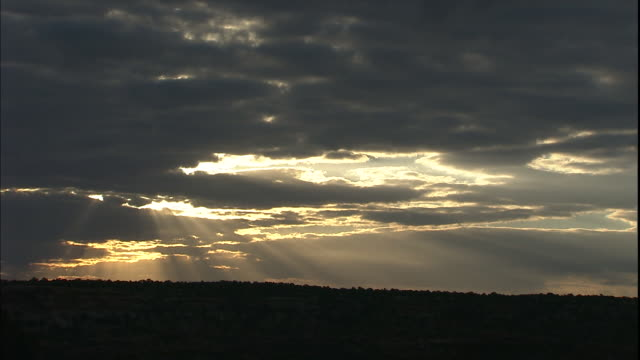 golden sun rays break through dark clouds in canyonlands national park, utah. - canyonlands national park stock videos & royalty-free footage
