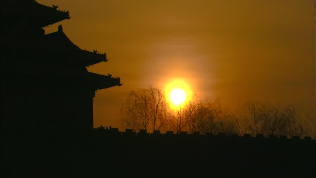 a golden sun rises beyond the forbidden city. - forbidden city stock videos & royalty-free footage