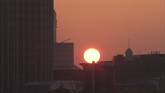 A golden sun rises over the rooftops of London. Available in HD.