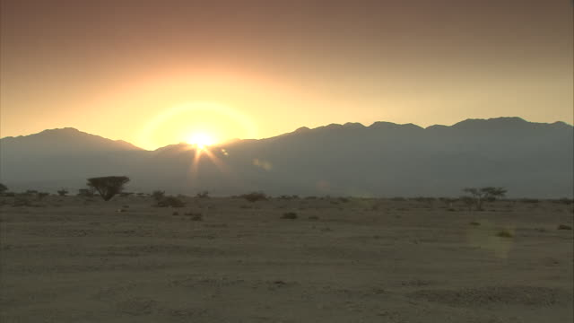 a golden sun rises past desert mountains in israel. - israel stock videos & royalty-free footage