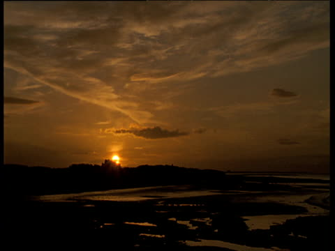 golden sun sets behind silhouette of bamburgh castle, sky and clouds reflect in pools of sea water covering beach in foreground, northumberland - northumberland coast stock videos & royalty-free footage