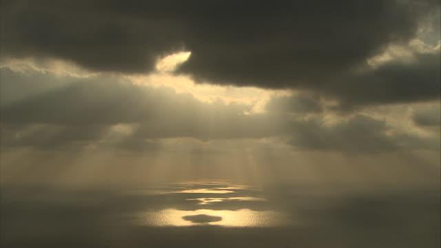 golden sunbeams shine through dark clouds and glow above the ocean. - ewigkeit stock-videos und b-roll-filmmaterial