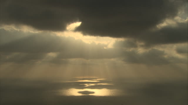 vídeos de stock e filmes b-roll de golden sunbeams shine through dark clouds and glow above the ocean. - céu vida após a morte