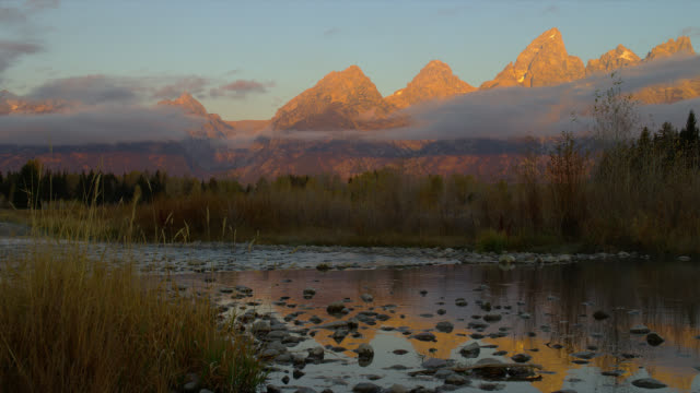 Golden sunlight glows across the peaks of the Grand Teton Mountains in Grand Teton National Park at sunrise.