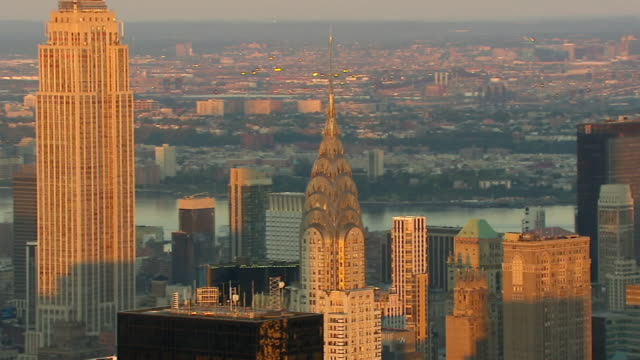 golden sunlight illuminates the chrysler building and empire state building at sunset. - chrysler building stock videos & royalty-free footage