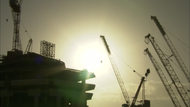 Golden sunlight shines above construction cranes at a high rise construction site.