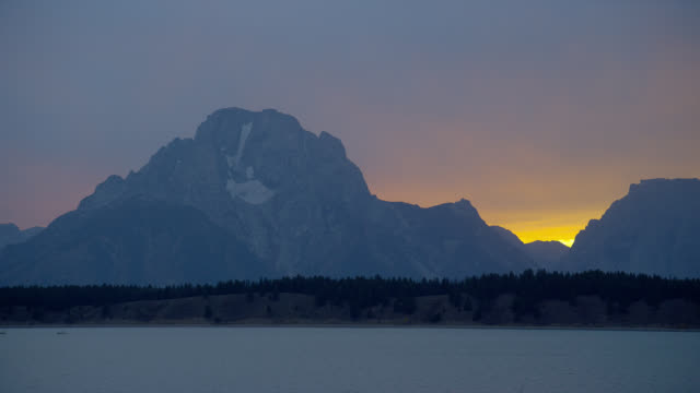 golden sunlight silhouettes mount moran and jackson lake in grand teton national park at sunset. - mt moran stock videos & royalty-free footage