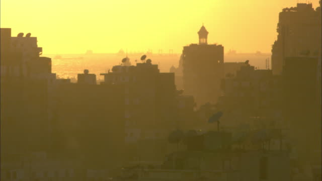 Golden sunlight suffuses the sky above Alexandria, Egypt.