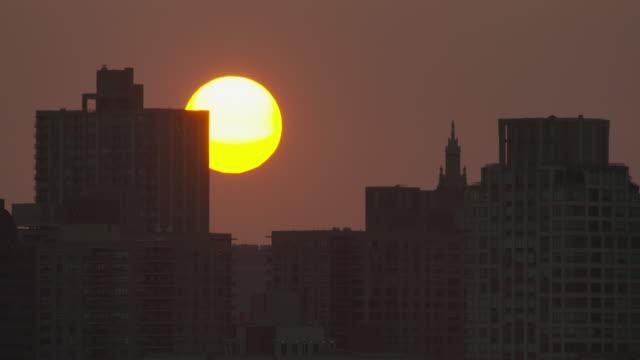 Golden sunrise above nondescript New York City buildings.