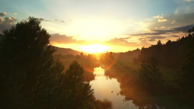 vídeos y material grabado en eventos de stock de reflexión de la antena amanecer dorado en la superficie del río - televisión de ultra alta definición