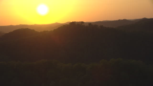 WS AERIAL golden sunset over hilly forests in Eastern Kentucky / Pikeville, Kentucky, United States