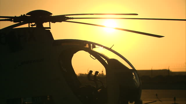 a golden sunset silhouettes a helicopter and rotors. - helicopter rotors stock videos and b-roll footage
