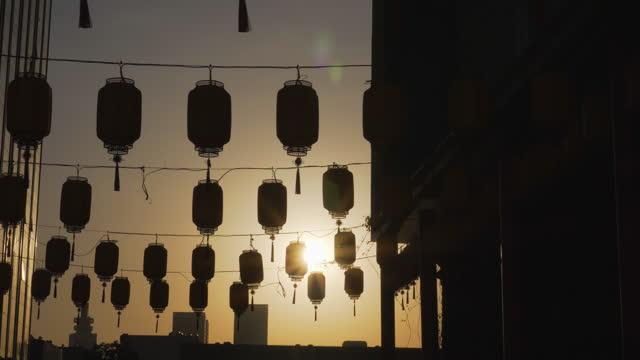 vidéos et rushes de golden sunset sun silhouettes rows of decorative street lights hanging across street - shanghai, china - arts culture and entertainment