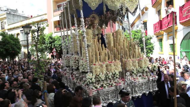 vídeos y material grabado en eventos de stock de golden trono a religious float being carried by the costaleros during semana santa, a procession through the streets of malaga, spain, europe - semana santa