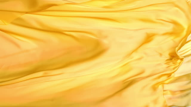 golden yellow metallic silky fabric flowing and waving horizontally in super slow motion and close up, white background - yellow stock videos & royalty-free footage