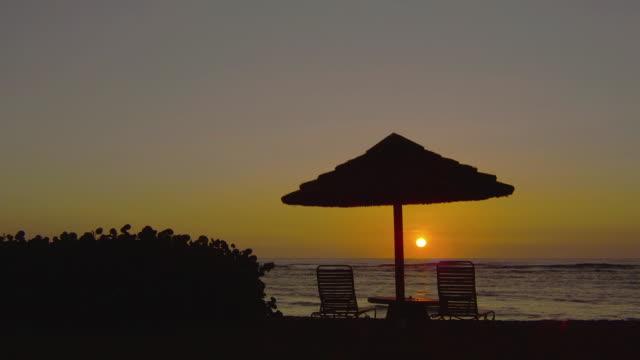 A golden-hour sky surrounds a table with a beach umbrella on a beach in Kauai, Hawaii.