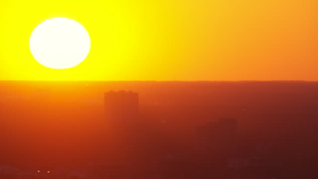 a golden-hour sun hangs above the horizon. - golden hour stock videos & royalty-free footage