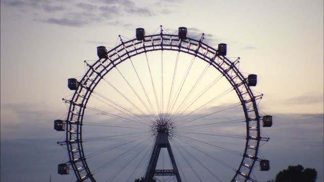 A golden-hour sun silhouettes the Riesenrad Ferris wheel in Vienna, Austria.