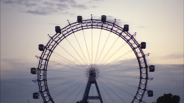 a golden-hour sun silhouettes the riesenrad ferris wheel in vienna, austria. - big wheel stock-videos und b-roll-filmmaterial
