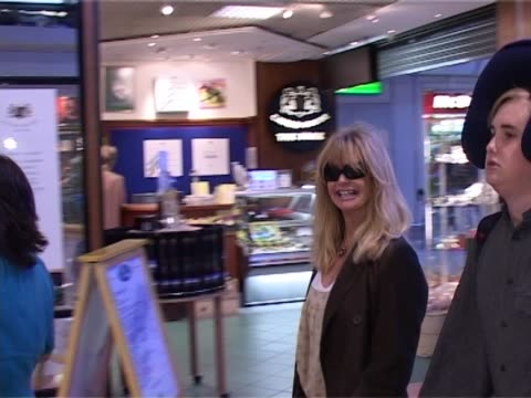 Goldie Hawn and her son Wyatt walk through Heathrow joking with photographers / Wyatt wears his inflight neck pillow on top of his head as they walk