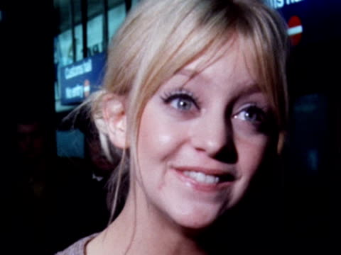 Goldie Hawn smiles and pulls faces for photographers as she arrives at London Airport with her husband Gus Trinkonis