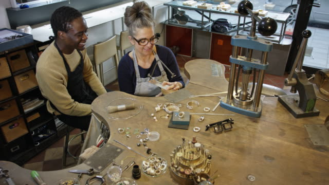 goldsmith workshop and retail shop led by independent master craftswoman with male apprentice of african origin. - männliche person stock-videos und b-roll-filmmaterial