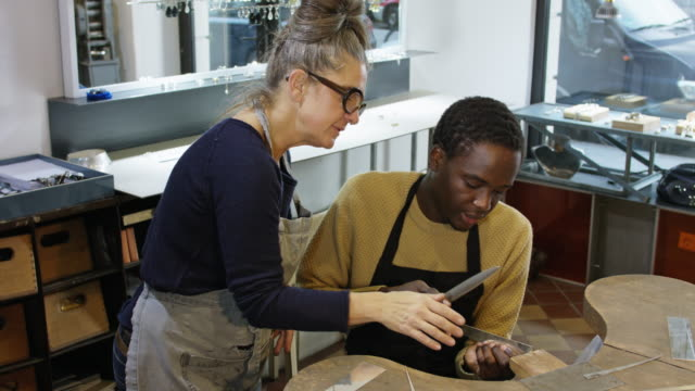 goldsmith workshop and retail shop led by independent master craftswoman with male apprentice of african origin. - direction stock videos & royalty-free footage