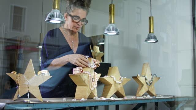 vídeos y material grabado en eventos de stock de goldsmith workshop and retail shop led by independent self-employed master craftswoman wearing a blue dress. - arte decorativo