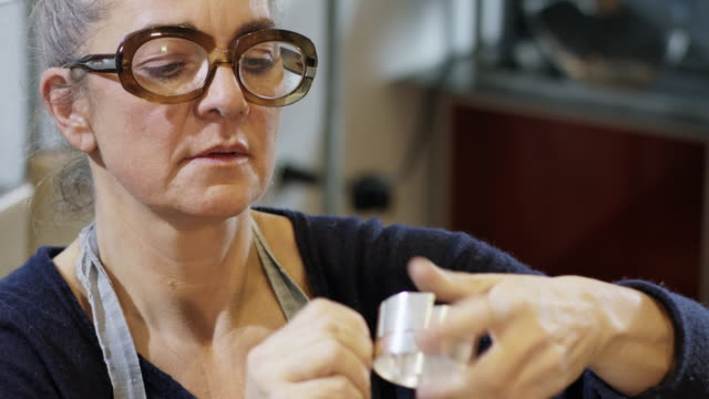 vidéos et rushes de goldsmith workshop and retail shop run by independent self employed master craftswoman in her 50s - preparing a silver bracelet for soldering. - exactitude
