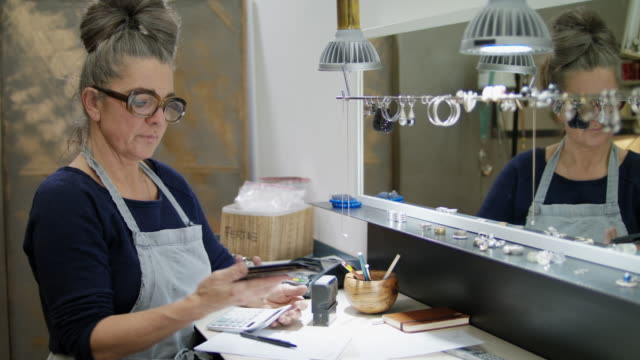 goldsmith workshop and retail shop run by independent self-employed master craftswoman is doing accounting. - schmuck stock-videos und b-roll-filmmaterial