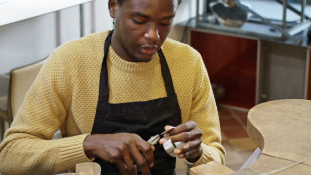 goldsmith workshop and retail shop with 33 years old male apprentice of african origin. - bracelet stock videos and b-roll footage