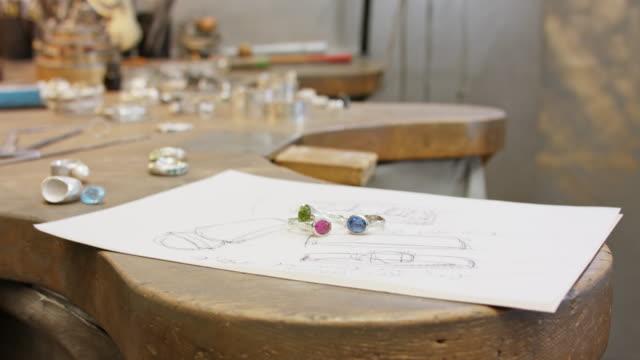 vídeos de stock e filmes b-roll de goldsmith workshop - rings on a sketch. - ring