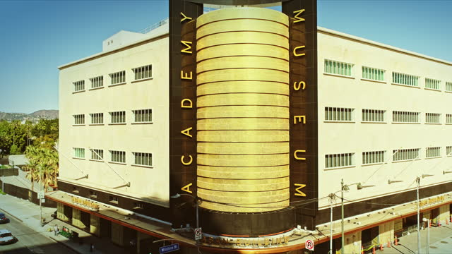 gold-tiled cylinder corner of historic department store structure built in 1939 in streamline moderne style now the academy museum of motion pictures facing the intersection of wilshire boulevard at fairfax avenue - academy of motion picture arts and sciences stock videos & royalty-free footage