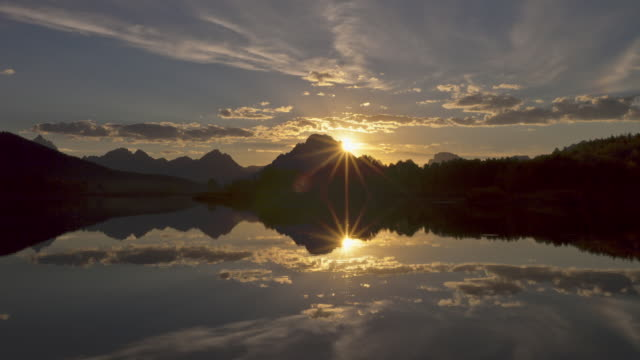 Gold-tinged clouds drift above the Snake River and Oxbow Bend in Grand Teton National Park, Wyoming.