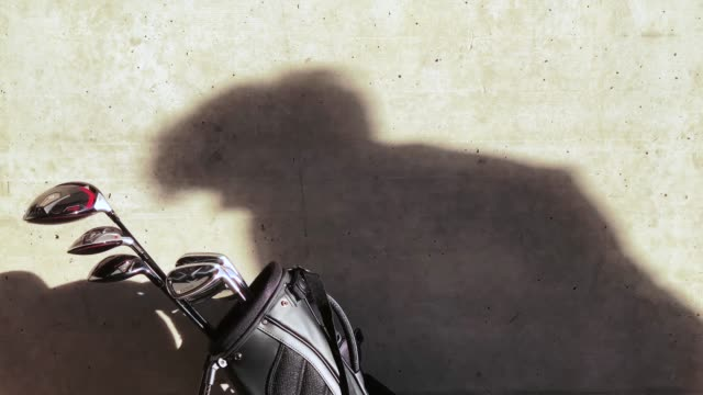 golf bag against a wall and shadow of a golfer making a golf swing - golf bag stock videos & royalty-free footage