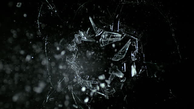 golf ball breaking pane of glass against black background, slow motion 4k - 壊れた点の映像素材/bロール