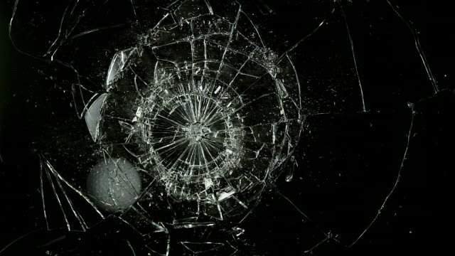 """Golf Ball breaking Pane of Glass against Black Background, Slow Motion"""