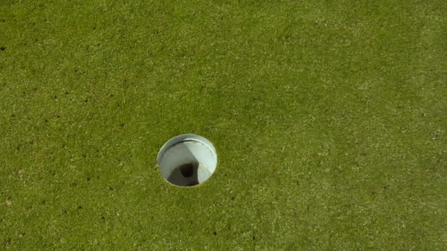 vidéos et rushes de cu, ha, golf ball falling into hole, man's hand removing it, north truro, massachusetts, usa - balle de golf