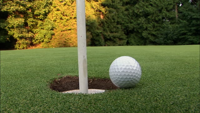 vidéos et rushes de cu, golf ball falling into hole - balle de golf