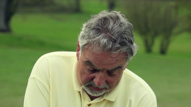 CU Golf ball hitting senior man's head, while he takes shot / Canterbury, Kent, UK