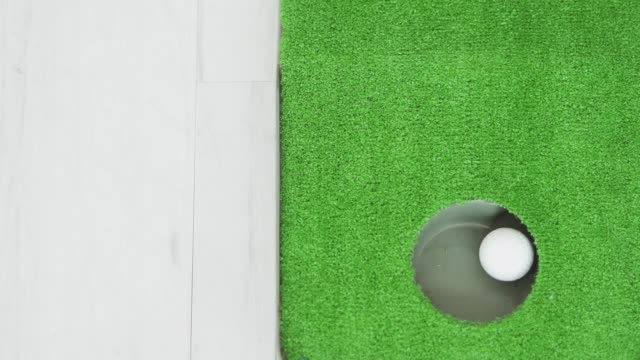 ein golfball rollt in ein loch - minigolf stock-videos und b-roll-filmmaterial