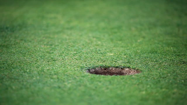 cu golf ball rolling into hole / palma de mallorca, mallorca, baleares, spain - golf stock-videos und b-roll-filmmaterial