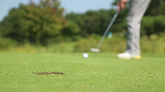 golf ball rolling into hole - golf stock-videos und b-roll-filmmaterial