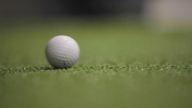 a golf ball rolling on the green - rolling stock videos & royalty-free footage