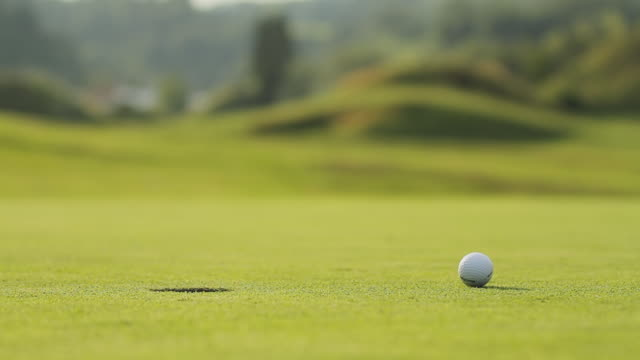 a golf ball rolling to the hole  - golfplatz green stock-videos und b-roll-filmmaterial