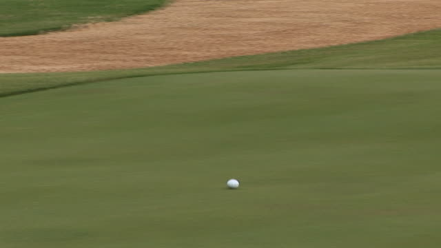 vidéos et rushes de a golf ball rolls along the green of a golf course. available in hd. - balle de golf
