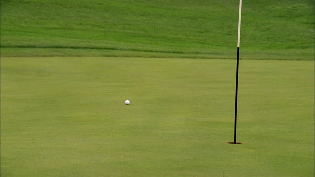 a golf ball rolls close to the hole on a putting green. - putting green stock videos & royalty-free footage