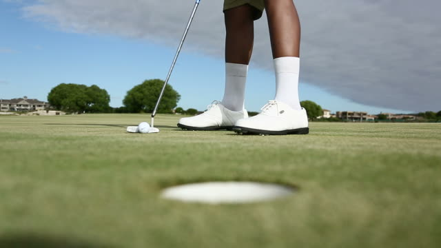 golf ball scores the hole on a golf course - golf shoe stock videos & royalty-free footage