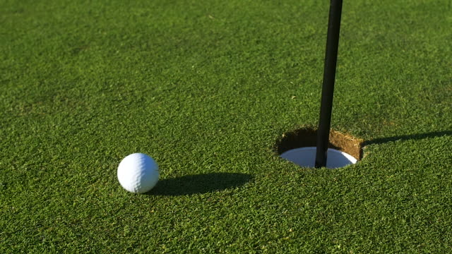 Golf ball travels across green to hole.